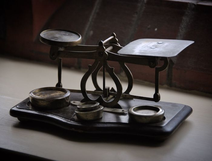 Close-up of antique weight scale on table