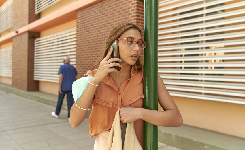 Young female businesswoman talking with her cell phone outdoors