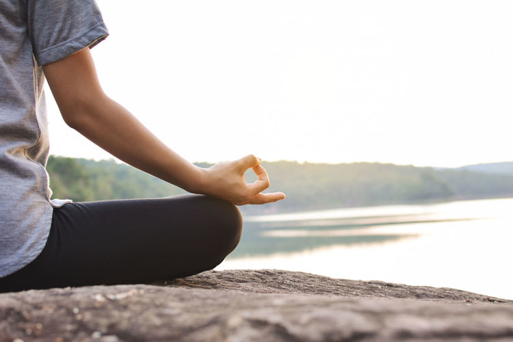 Cropped image of woman practicing yoga while sitting on rock