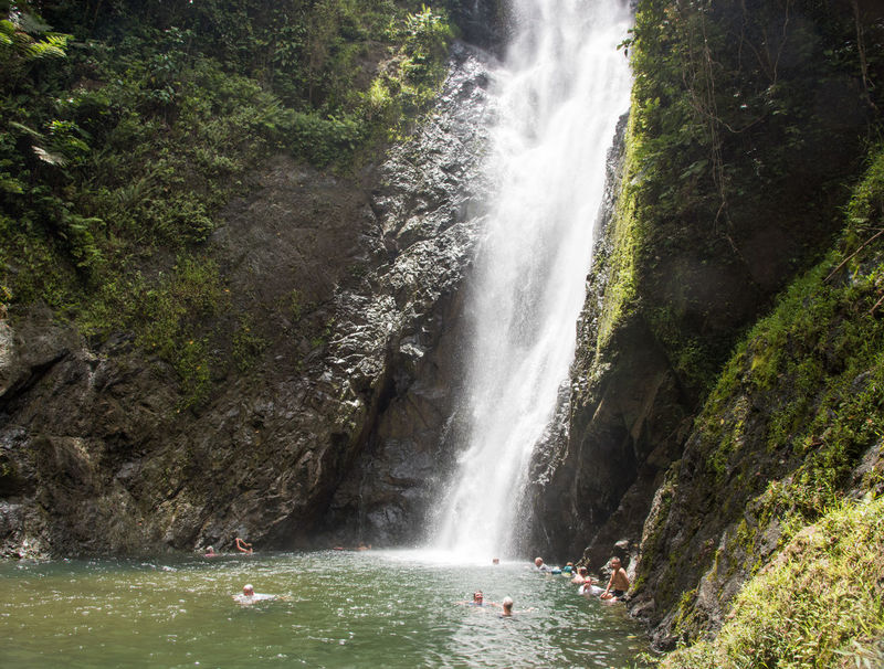 SUVA,FITI LEVU,FIJI-NOVEMBER 28,2016: Swimming in rock pool with cascading waterfall in remote rainforest in Suva, Fiji Exploring Rock Face Suva Swimming Tranquility Adventure Beauty In Nature Cascading Cliff Enjoying Life Geology Large Group Of People Long Exposure Motion Nature Outdoors Pacific Islands People Real People Rock Pool Scenics Travel Destinations Vacations Water Waterfall