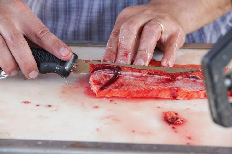 Close-up of man cutting fish