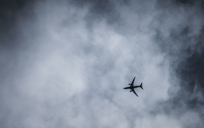 Low Angle View Of Airplane Flying Against Cloudy Sky