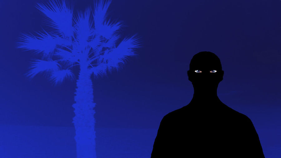 Rear view of silhouette man standing against blue sky