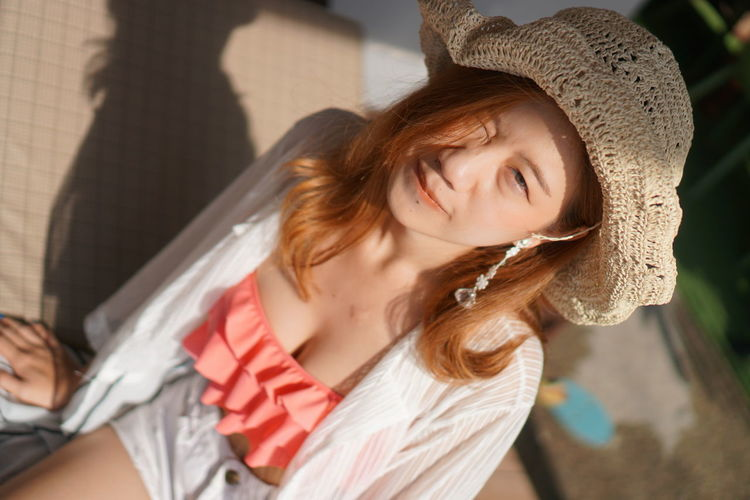 High angle portrait of young woman wearing hat while winking