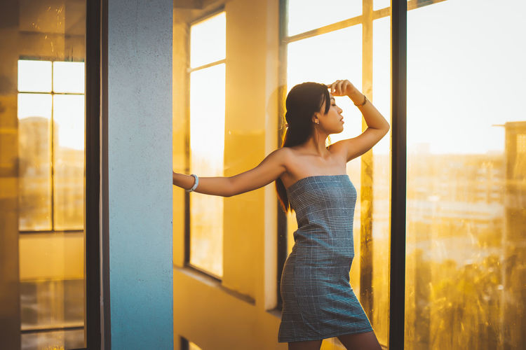 One Person Window Real People Standing Young Adult Lifestyles Leisure Activity Indoors  Young Women Casual Clothing Women Three Quarter Length Glass - Material Day Architecture Sunlight Adult Built Structure Beautiful Woman Hairstyle Contemplation Arms Raised