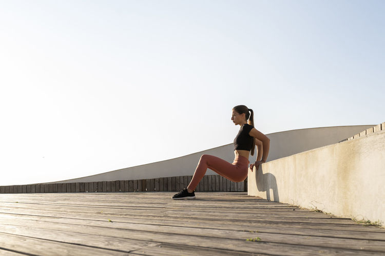 Young woman on wall against clear sky