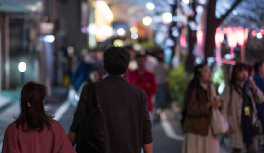Rear view of people walking on street at night