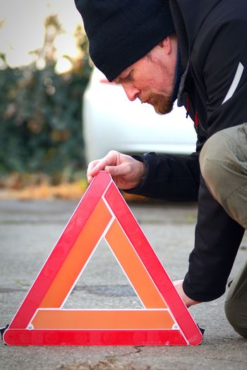 Midsection of man positioning red safety triangle  while standing on street