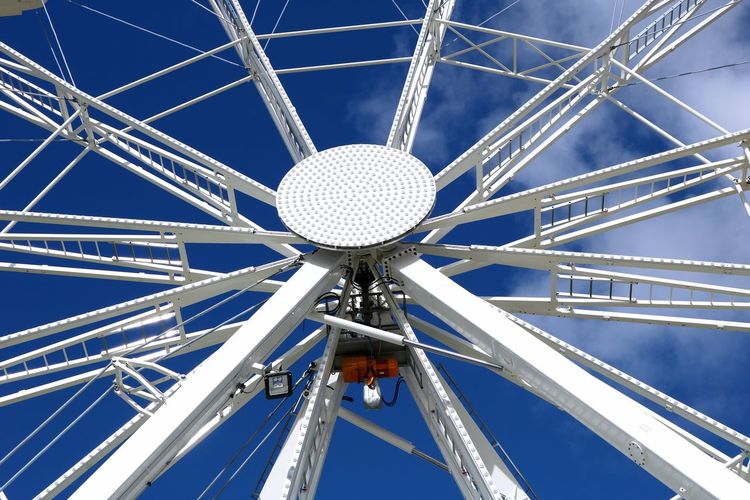 Low angle view of ferris wheel against blue sky