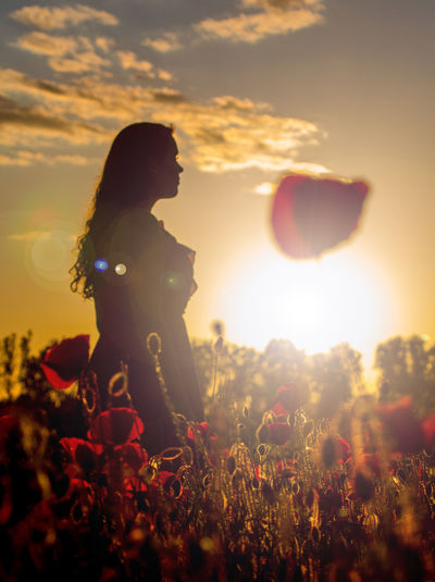 Silhouette woman on field against sky during sunset