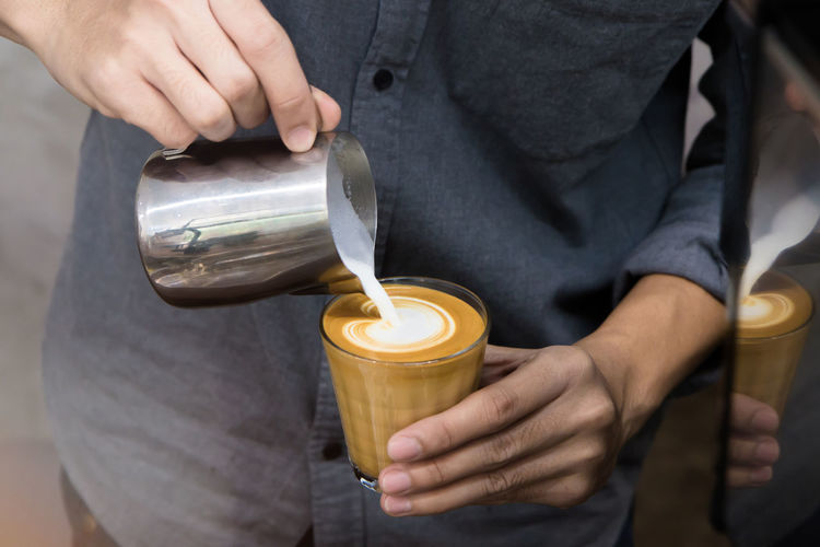 Midsection Of Man Pouring Cream In Coffee
