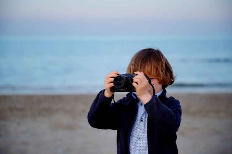 Boy photographing from camera at beach