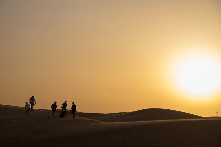 People in desert against sky during sunset