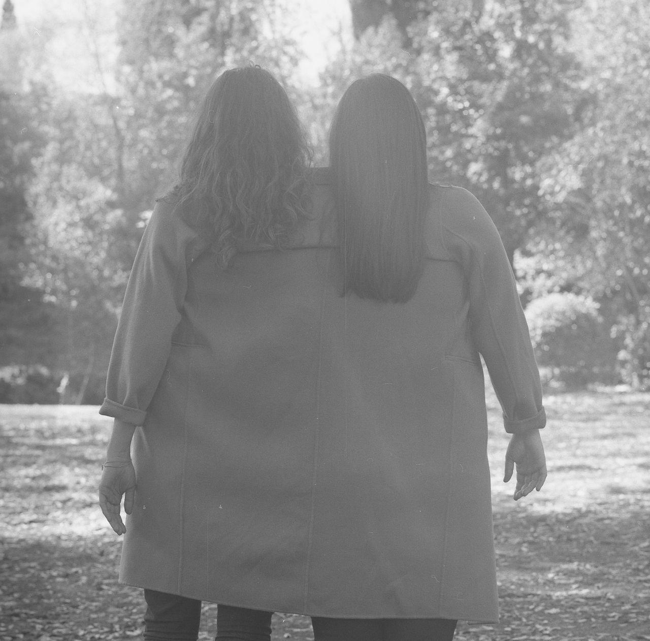 Lesbian couple wearing jacket in forest