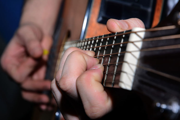 Midsection of man playing guitar indoors