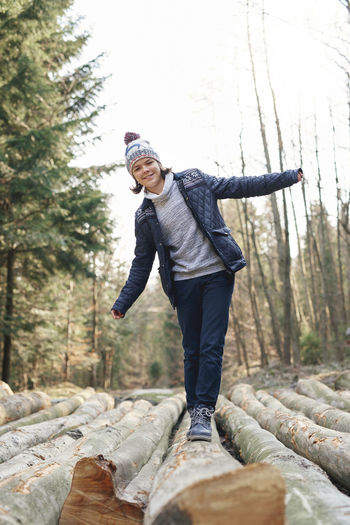 Smiling teenage boy standing on log against sky