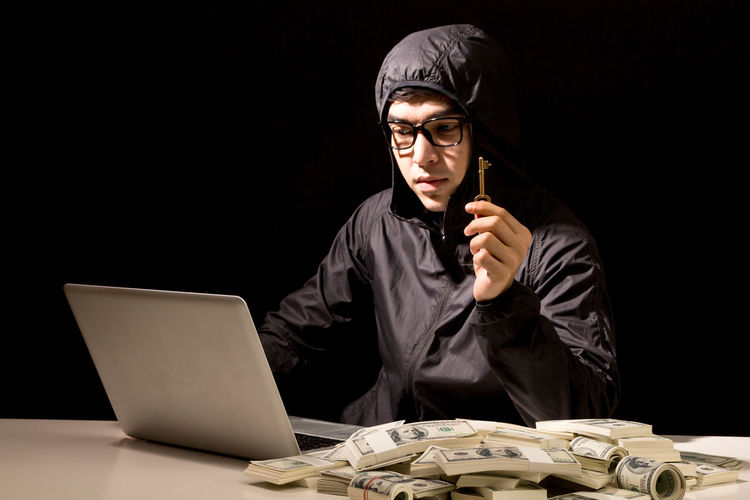 Computer hacker using laptop by paper currency at table against black background