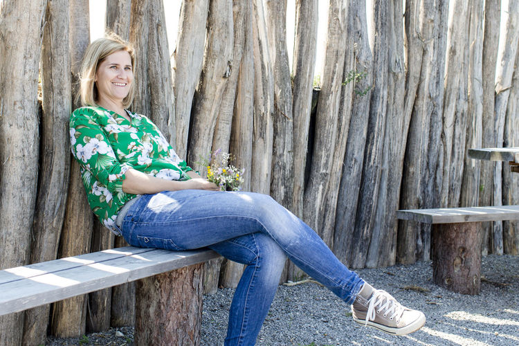 Smiling woman sitting on bench against fence