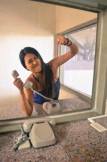 Woman holding telephone seen through glass