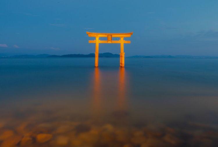 Torii gate in sea against blue sky