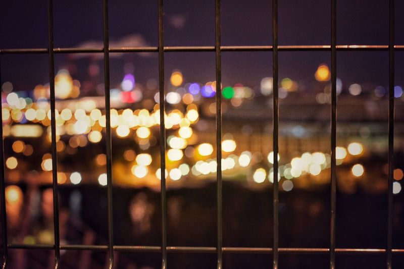 High Angle View Of Illuminated Lights In City Seen Through Window At Night