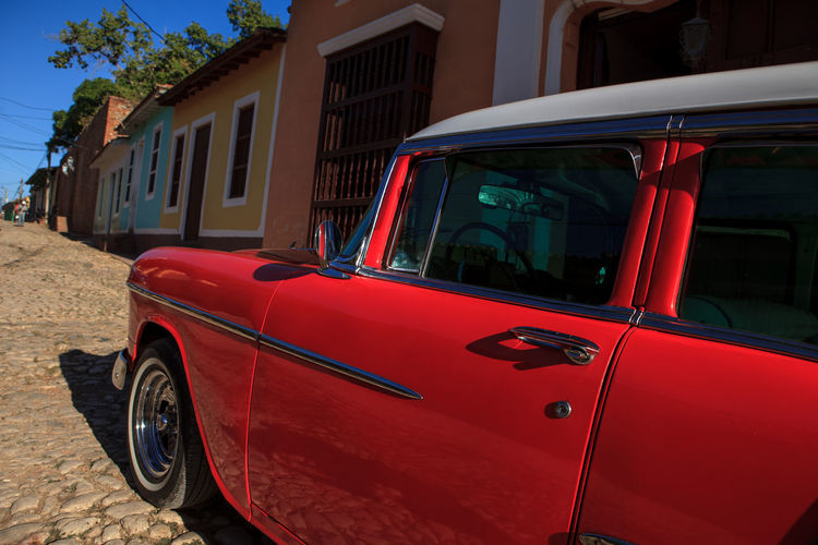 Red vintage car on footpath against houses