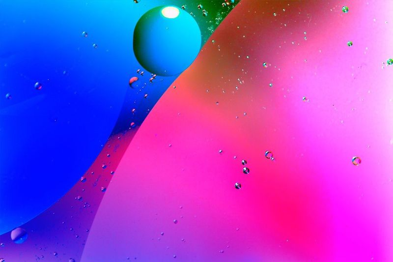 Close-up of multi colored balloons against blue water