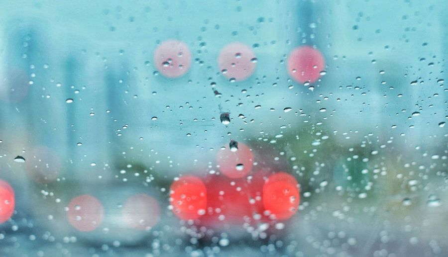 Close-up of wet window in rainy season with tail light bokeh