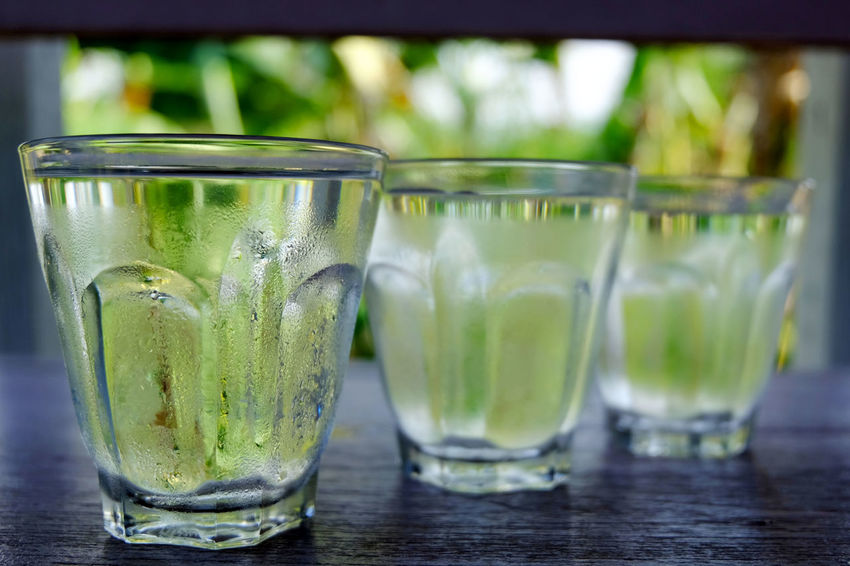 Row of water glass on wooden table on bright green background Cool Pure Bevarage Cold Temperature Drink Drinking Glass Fresh Freshness Glass Healthy Healthy Eating Lifestyles Purity Refreshing Refreshment Summer Thristy Water