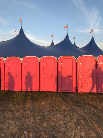 Shadows Of People On Red Portable Toilets Against Tent