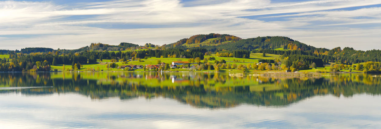 Panorama landscape with alps mountains mirroring symmetric in lake Forggensee nearby city Füssen in region Allgäu, Bavaria in Germany, Allgäu Bavaria Panorama Beauty In Nature Forggensee Germany Lake Landscape Mirroring In Water Mountain Range Nature No People No People, Outdoors Panoramic Landscape Reflection Rural Landscape Rural Scene Scene Scenics Summer Symmetry Tranquil Scene Water Wide Angle