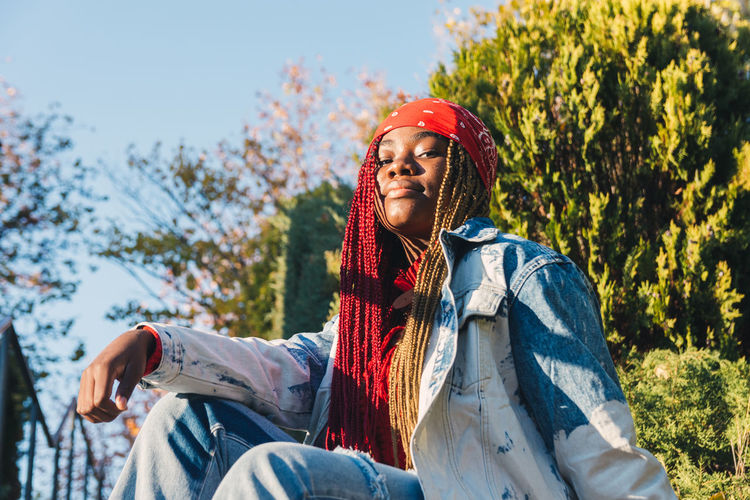 Portrait of a black girl with colored braids sitting on a staircase. dressed with a vintage denim ja