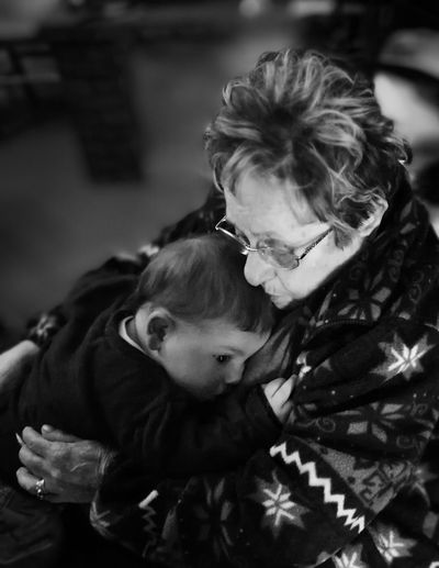 Grandmother embracing grandson while sitting at home