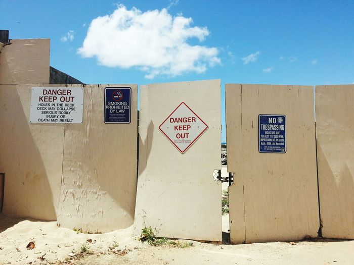 Various sign boards on fence against sky
