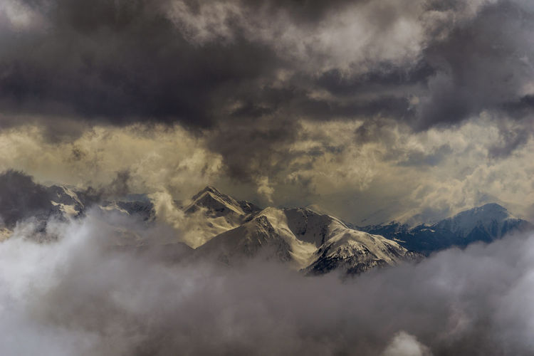 Aerial View Of Snowcapped Mountains Against Cloudy Sky