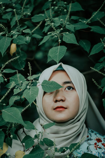 Woman In Hijab Standing Against Tree