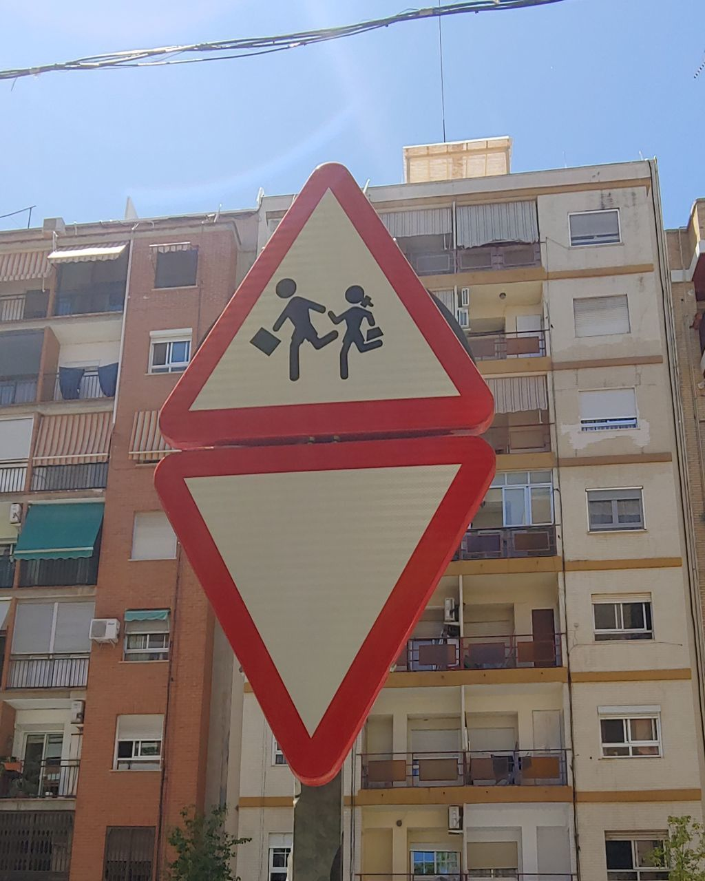 built structure, building exterior, architecture, communication, sign, building, city, sky, road sign, no people, day, road, low angle view, warning sign, outdoors, residential district, triangle shape, information sign, nature, information, apartment