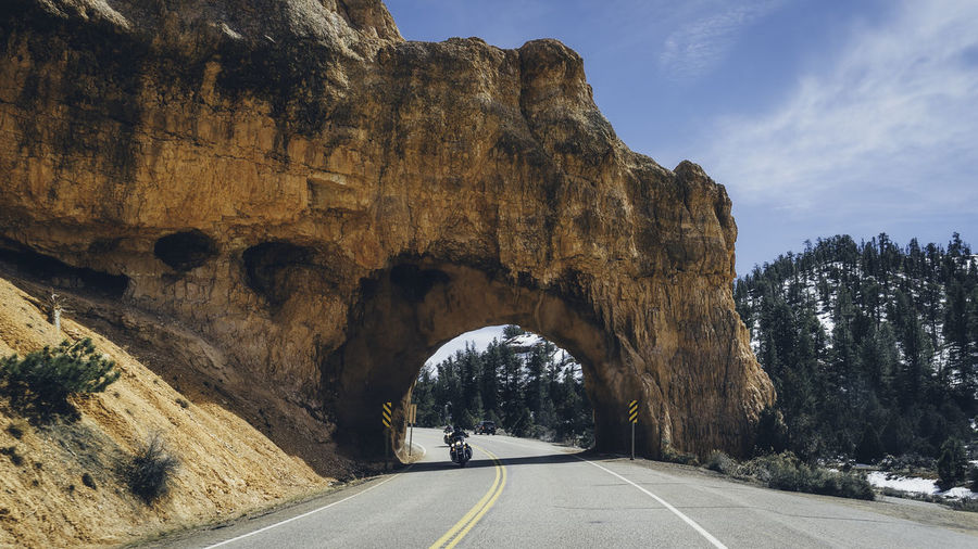 Road leading towards rock formation against sky