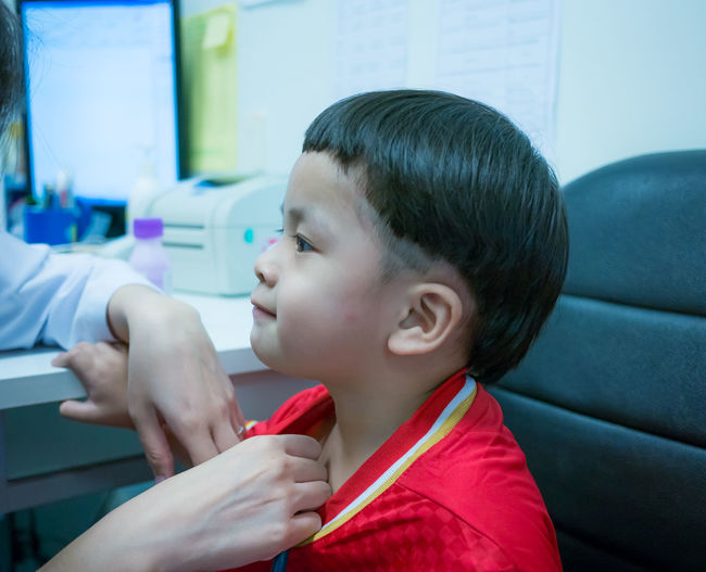Cropped Hand Of Doctor Examining Boy At Clinic
