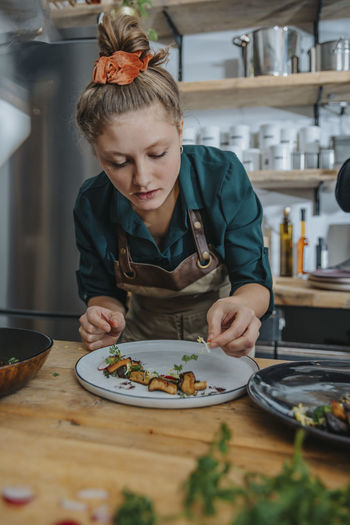 Portrait of a woman preparing food in kitchen