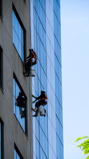 Low angle view of people working on modern building