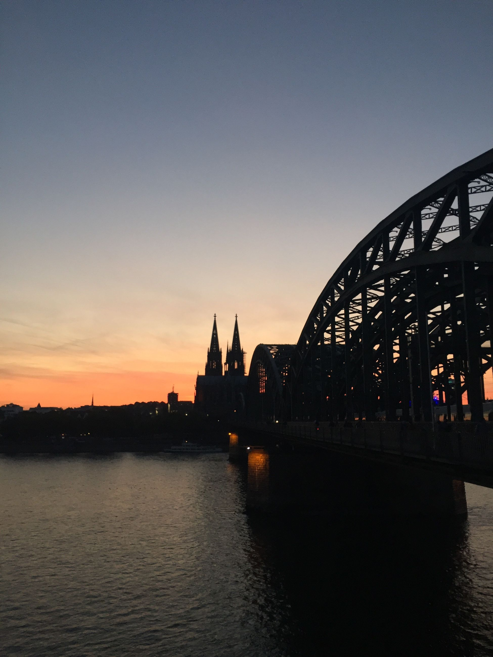 built structure, architecture, building exterior, travel destinations, tourism, silhouette, water, famous place, waterfront, dusk, river, sunset, city, bridge - man made structure, travel, spirituality, international landmark, place of worship, capital cities, city life, outdoors, riverbank, engineering, church, sydney harbor bridge, sky, spire, vacations, outline