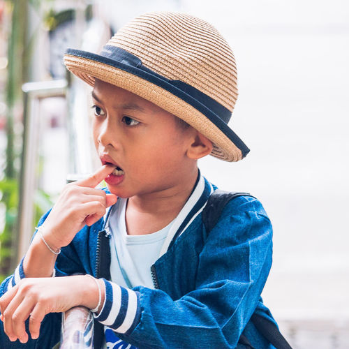 Thoughtful boy with finger in mouth