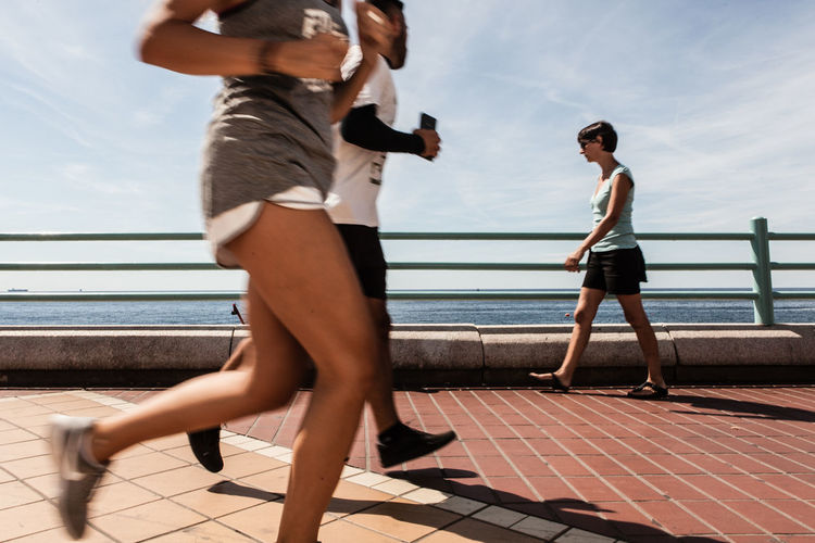 Athlete jogging on promenade by sea against sky