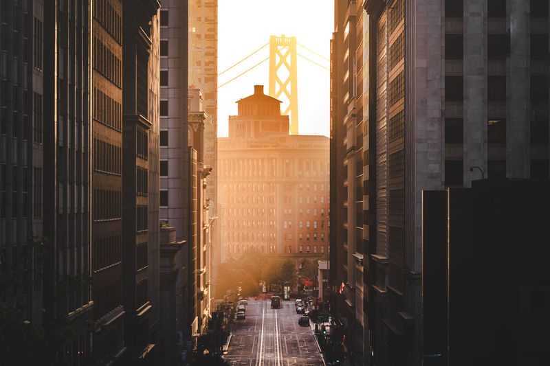 Street amidst buildings in city against sky during sunset