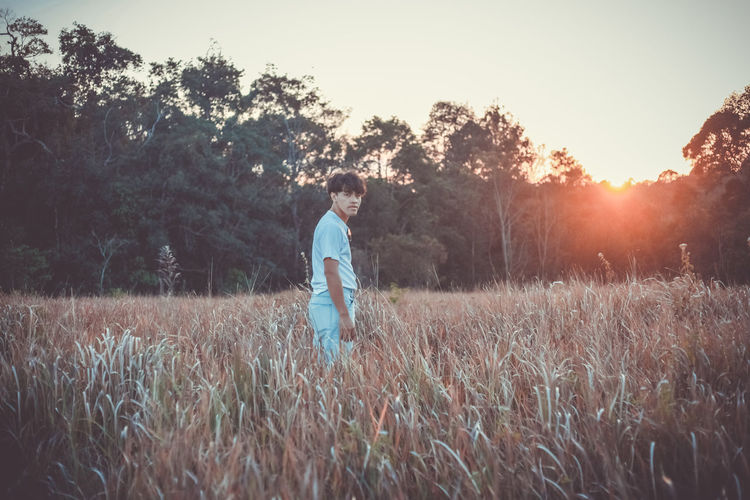 Young man standing on field against sky during sunset