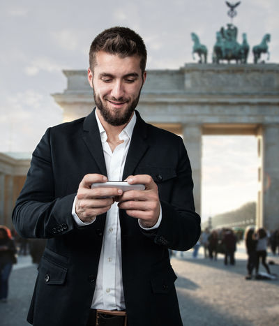 Attractive man is standing in front of the brandenburger gate in berlin and plays with his smartphone Berlin Light SMS Writing Architecture Beard Branderburgertor Built Structure Businessman Communication Day Front View Leisure Activity Lifestyles One Person Outdoors People Selfie Smart Phone Standing Sun Urban Well-dressed Wireless Technology Young Adult Discover Berlin