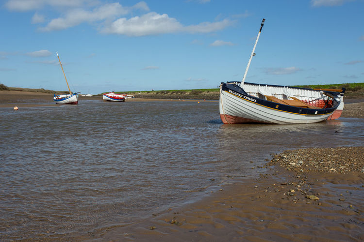 Moored sailing boats at low tide, Burnham Overy Staithe, Norfolk, United Kingdom Mode Of Transportation Transportation Nautical Vessel Water Sky Cloud - Sky Sea Moored Beach Day Nature Land Travel Sand Beauty In Nature Scenics - Nature Outdoors Non-urban Scene Anchored Low Tide Fishing Boat Yacht Burnham Overy Staithe Norfolk Uk Copy Space Sailing Sailing Boat Admiral Nelson Sun Sunny