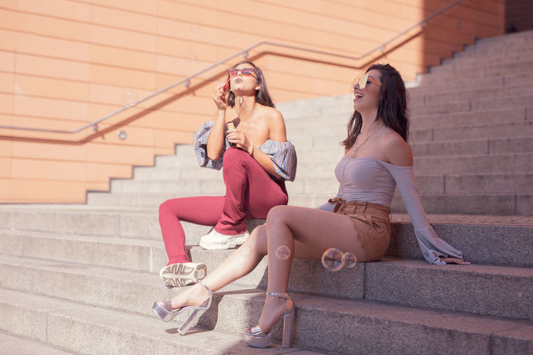 Young women playing with bubbles while sitting on steps