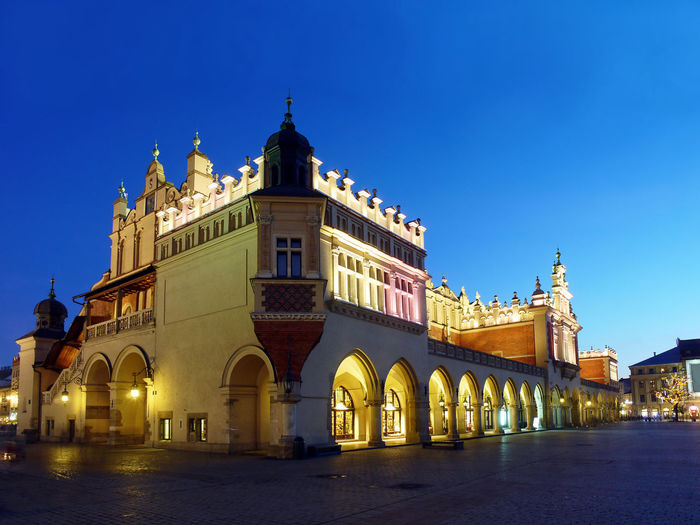 Gothic Cloth Hall Sukiennice on the Main Market Square in Krakow by night Arcade Arcades Architecture City Cloth-hall Cracow Europe European  Evening Gothic Historical Illumination Krakow Light Lighting Main Market Square Medieval Monument Night Night-time Ornaments Sukiennice Tourism Tourist Tourists Town Travel Landmark
